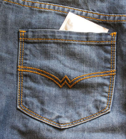 Condoms in package in the pocket of a blue jeans. Condoms to prevent sexually transmitted infections. Copy space 免版税图像
