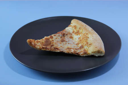 Dried slice of pizza on a black table on a blue background. Food concept. 写真素材