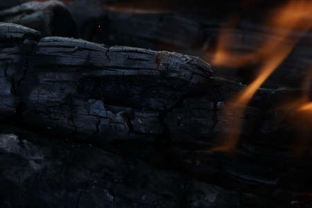 Smoldered logs burned in vivid fire close up. Atmospheric background with flame of campfire. Unimaginable detailed image of bonfire from inside with copy space. Whirlwind of smoke and glowing embers. Stock Photo