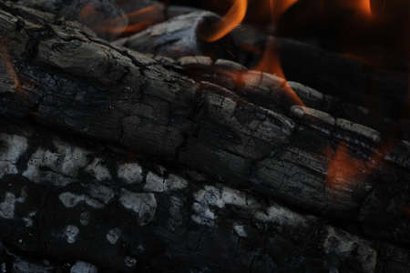 Smoldered logs burned in vivid fire close up. Atmospheric background with flame of campfire. Unimaginable detailed image of bonfire from inside with copy space. Whirlwind of smoke and glowing embers.