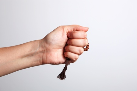 A woman's hand holding a rosary in a fist Stock Photo - 11159897
