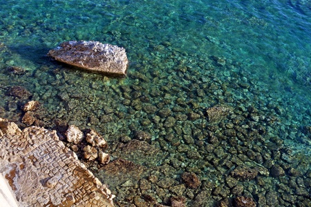 seawater: Transparent clear seawater, seabed visible, large rock and rocky shore