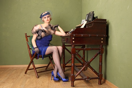 typist: A beautiful young typist dressed in the style of 1920s sitting at the table with the typewriter.