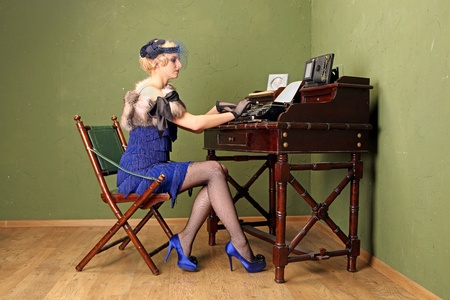 A beautiful young typist dressed in the style of 1920s working on the typewriter. photo