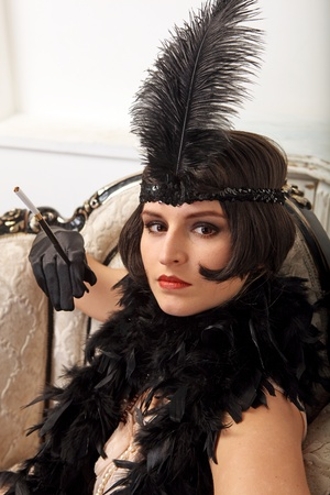 feather boa: A beautiful young girl dressed in the style of 1920s, sit in the armchair and hold cigarette holder.