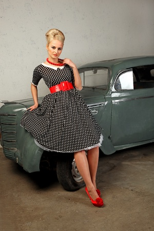 A beautiful young girl dressed in the style of 1950's, standing near an old car. photo