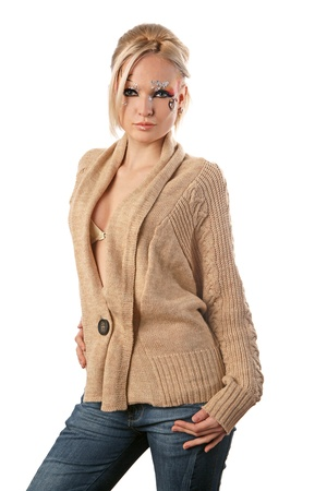 A young pretty blond girl with a bright fantasy make-up dressed in a woolen cardigan. photo
