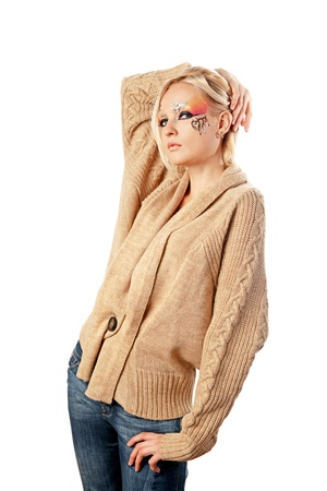 A young pretty blond girl with a bright fantasy make-up dressed in a woolen cardigan.