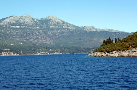 Mountains by the sea in Montenegro with a small town at the foot of it. Adriatic Sea. photo