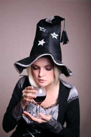 Pretty young witch in black and silver costume conjuring with a potion photo