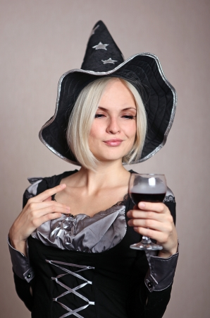 Pretty young witch in black and silver costume with a potion photo