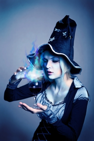 conjuring: Pretty young witch in black and silver costume conjuring with a potion