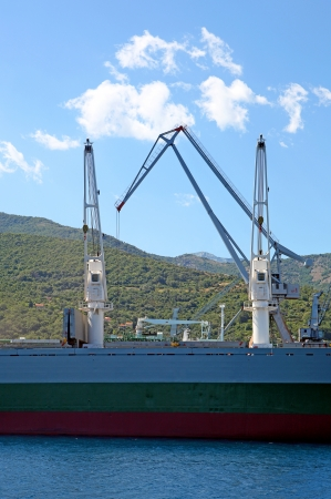 A dry cargo ship with cranes on water, with hills and blue sky on the background.
