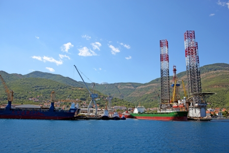 Dry cargo ships, floating cranes and oil platform with hills and blue sky on the background.