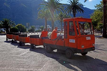 garbage collector: Recolectores de basura va a trabajar en un coche rojo con remolque. Kotor, Montenegro. Editorial