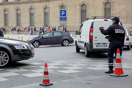 controling: A policeman at a crossroads controling street traffic in Paris, France.
