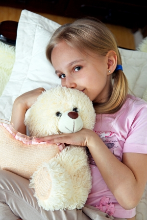 Cute little blond girl hugging a teddy bear. photo