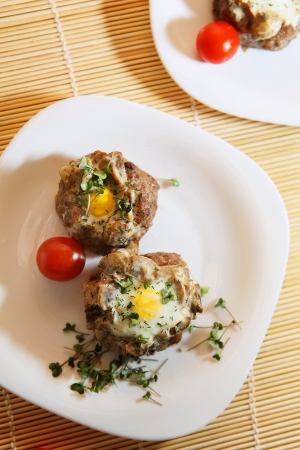 broccoli sprouts: Delicious quail eggs in the minced meat with mushrooms, decorated with cherry tomatoes and broccoli sprouts on white plates. Stock Photo