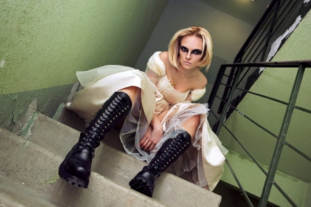 Beautiful young blond girl dressed like a gothic bride on the stairs. photo