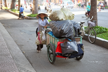 indigence: An old beggar woman with a trolley going to pass on the Waste. Saigon, Vietnam.