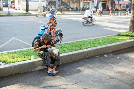 indigence: An old beggar man sitting on the sidelines eating. Saigon, Vietnam. Editorial