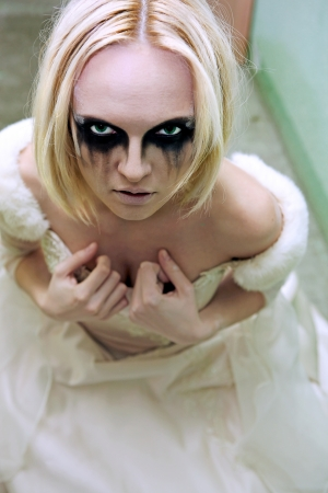 Beautiful young blond girl dressed like a sad gothic bride. photo
