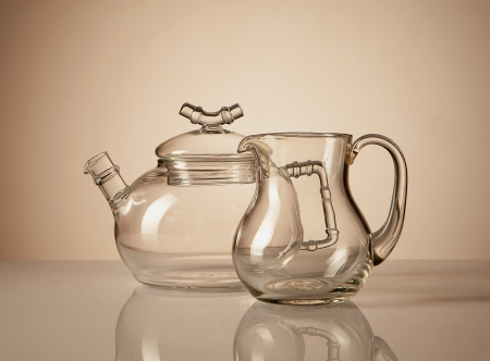 A glass teapot and a creamer with a reflection on the gradient background. photo