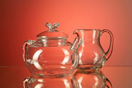 creamer: A glass teapot and a creamer with a reflection on a red background.