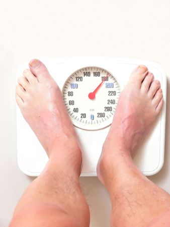 A man on the bathroom scale finds hi is to heavy and needs Stock Photo - 739015