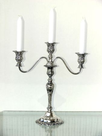 tarnish: A silver three arm candle holder with white candles.    50190