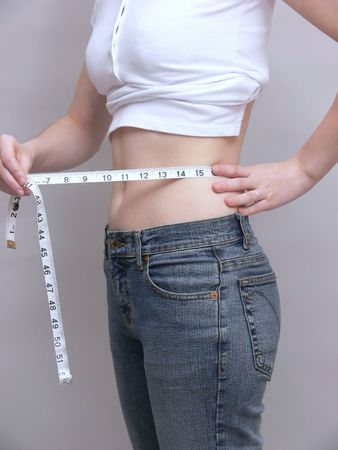 A young girl is measuring her waist for weight lose.  50507