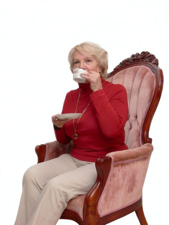 Senior citizen   40774  A senior citizen sitting in a armchair with a cup of coffee in her hand.