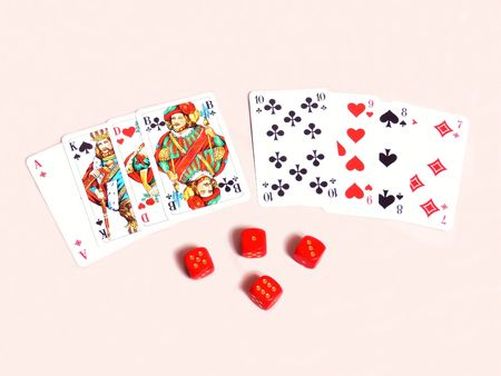Cards and dices  50865    An deck of cards and 4 red dices on very light beige background.