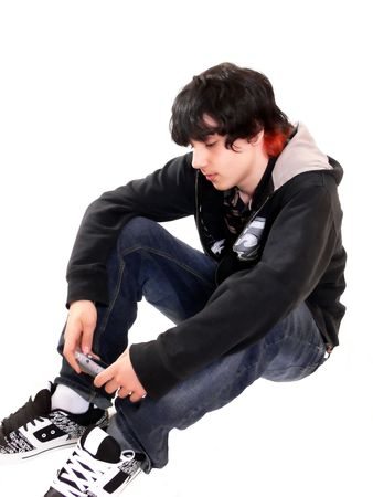 Teen boy sitting  60776  A teenage boy is sitting on the floor in the studio with his game boy on white background. Stock Photo