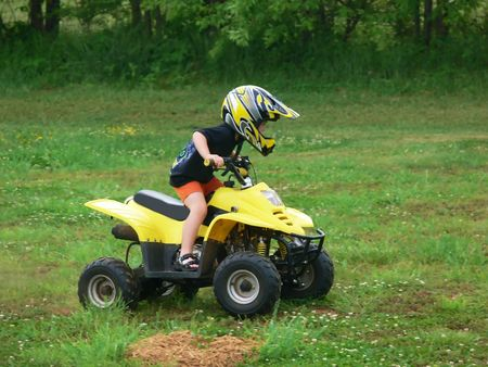 A boy on his an all-terrain vehicle on a field.
