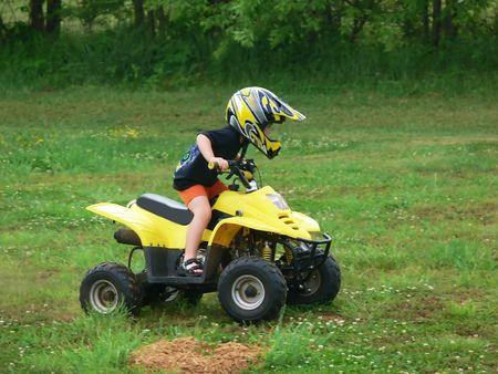 4 wheel: Un muchacho en el suyo un veh�culo todo terreno en un campo.
