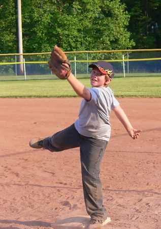 shortstop: Baseball player   70147 A young baseball player in training on late afternoon with his team.      Stock Photo