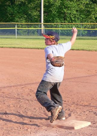 shortstop: Baseball player  70137 A young baseball player in training on late afternoon with his team.      Stock Photo