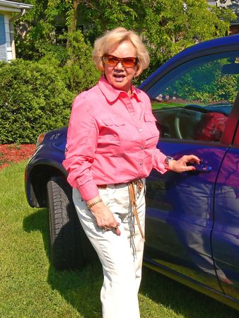 Lady with blue car. An senior citizen with her new blue SUV on the front lawn of her house.
