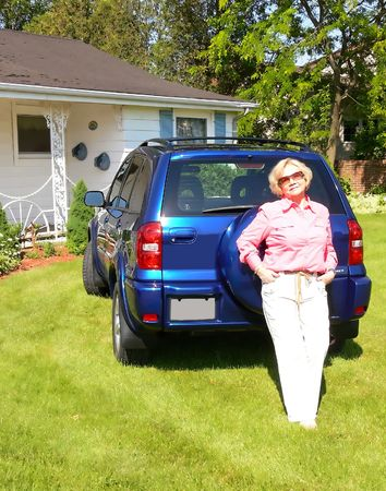 Lady with blue car. An senior citizen with her new blue SUV on the front lawn of her house. photo