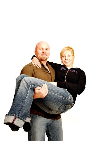carrying: A man carrying his girlfriend in an studio for white background. Stock Photo