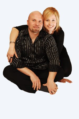 Young lovers sitting on the floor in an studio for light blue background.