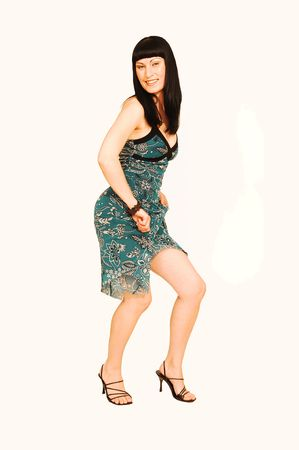 A young pretty woman standing in an studio wearing a green dress with black ornaments printed on Stock Photo - 3611634