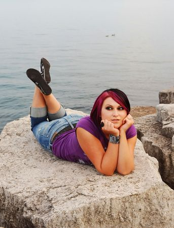 An red hair girl in jeans lying on the shore of lake Ontario at sunset.