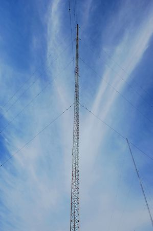 Wide angel shot of a radio tower from below in the blue sky.