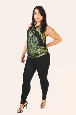 A young woman in black tights and nice round figure standing in an studio with black hair and high heels on white background.
