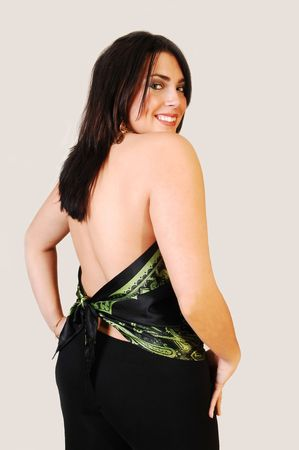 An black haired woman with a bare back looking over her shoulder and smiling in the camera.  photo