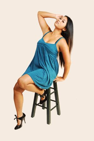 sexy asian woman: An beautiful young Asian woman with long black hair in a blue dress sitting on a bar chair.