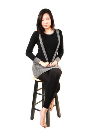 An beautiful young Asian woman with long black hair and tights sitting on a bar chair.