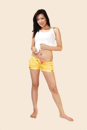 pink panties: Lovely Asian lady in an white top and yellow shorts standing on the floor with  nice long black hair, shooing her pink panties.  Stock Photo